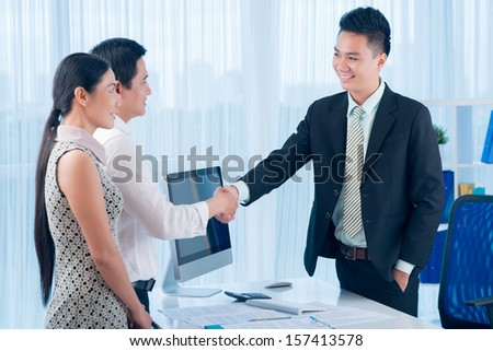 Image of a family couple shaking hand to their financial advisor after successful dealing on the foreground