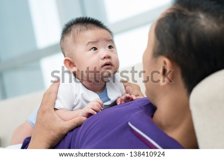 Image of a father holding his newborn son - stock photo