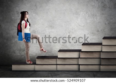 Image of a female college student walking upward on the books stair. Concept of study hard