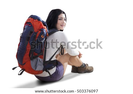 Image of a female hiker sitting with backpack while smiling and looking at the camera, isolated on the white background
