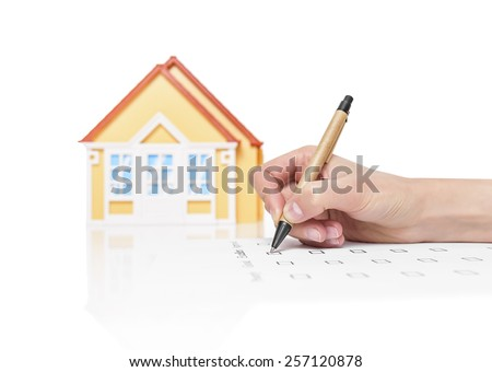 Image of a female signing a deed of sale, mortgage document or insurance contract on a house with a closeup view of his hand with a small model of a house. - stock photo