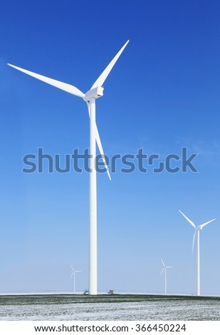 Image of a field with windturbines covered by snow in winter.