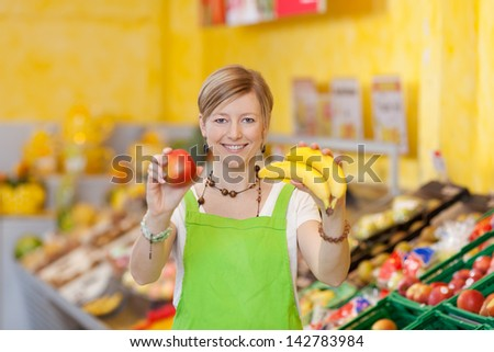 Image of a friendly saleswoman showing different fruits at the food counter in a supermarket. - stock photo