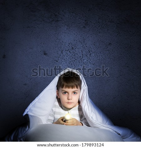image of a frightened boy under the covers with a flashlight