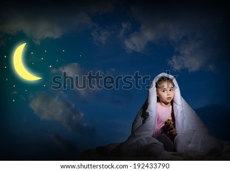 image of a frightened girl under the covers with a flashlight - stock photo