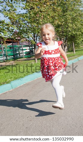Image of a girl running down the road - stock photo