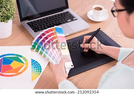 image of a graphic designer using graphic tablet in her work on the foreground and working with color samples for selection. A concept of modern digital workplace  - stock photo