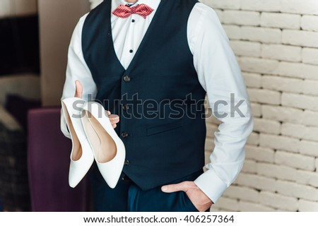 image of a groom holding bridal shoes. - stock photo