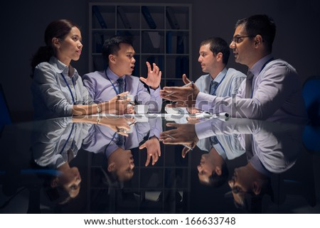 Image of a group of businesspeople discussing the business plan emotionally before the deadline during the night - stock photo