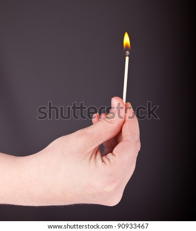 Image of a hand holding a lit match. - stock photo