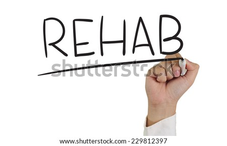 Image of a hand holding marker and write Rehab word isolated on white