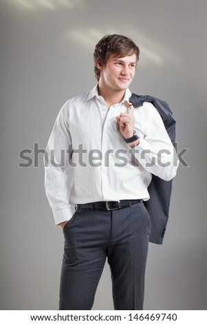 image of a handsome business man smiling shyly with his gray suit jacket hooked over his shoulder - stock photo