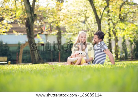 Image of a happy young family spending time outdoor on a sunny summer day  - stock photo