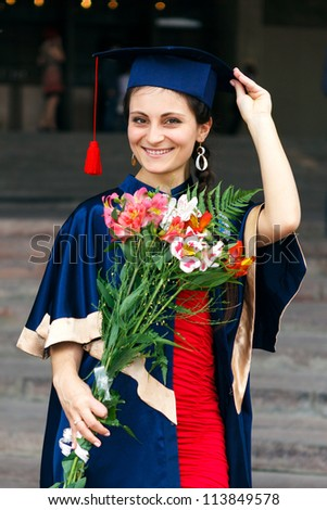 Image of a happy young graduate with flowers - stock photo