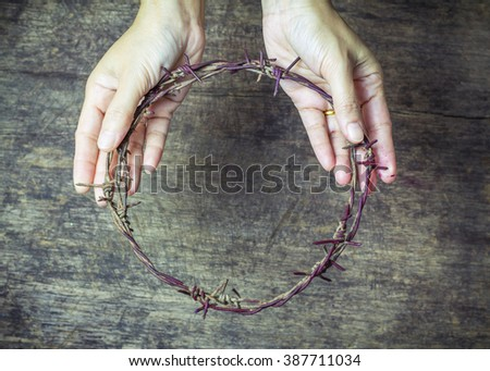 image of a lady hands holding old metal Barbed Wire made like the crown of thorns of Jesus  can be used for Christian concept , easter concept - stock photo