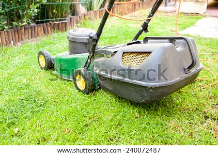Image of a lawn mower in a household garden cutting grass