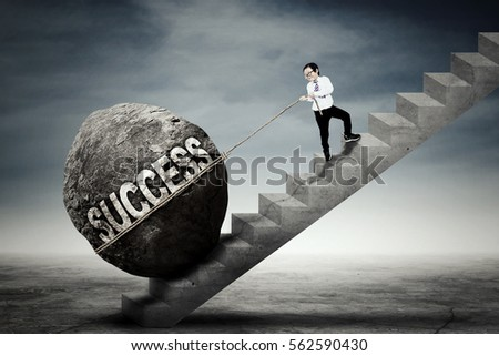 Image of a little businessman pulling upward a big stone with success word on the stairs