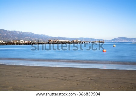 Image of a long exposure in Santa Barbara Harbor California with famous Stearns Wharf lining the blue water. - stock photo