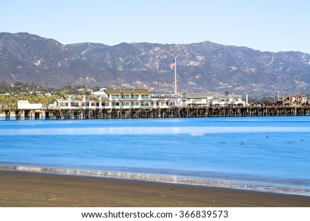 Image of a long exposure in Santa Barbara Harbor California with famous Stearns Wharf lining the blue water.