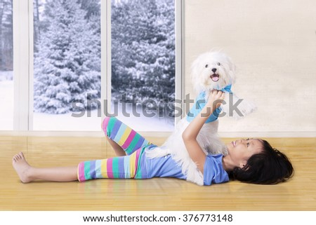 Image of a lovely little girl lying on the floor while lifting her puppy - stock photo