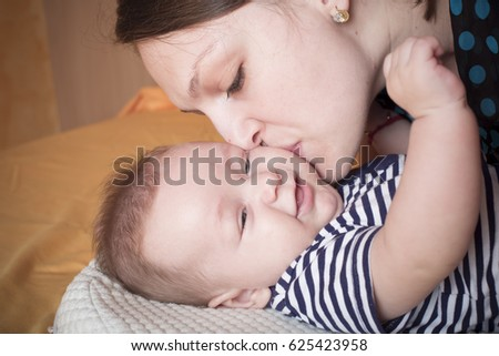 Image of a loving mother kissing her baby son in the bedroom