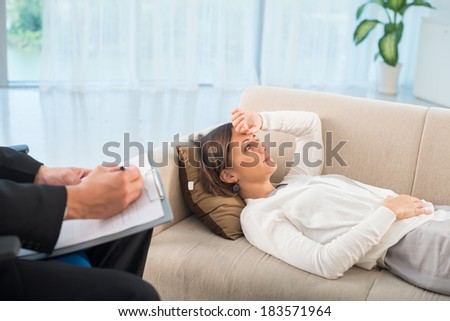 Image of a lying female patient deep in her problems while psychologist making notes on the foreground
