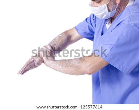 Image of a male doctor wearing a medical mask washing his hand on a white background - stock photo