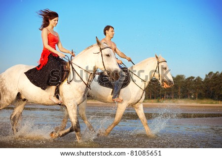 Image of a man and a woman in love with the sea on horseback - stock photo