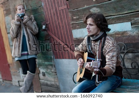 Image of a man playing the guitar and a woman pictures him. - stock photo