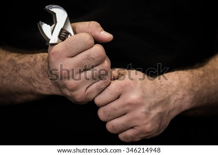 Image of a man's hands holding a wrench against a black background