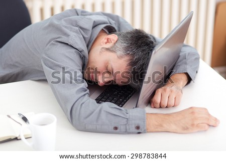 Image of a man sleeping at the working desk  - stock photo