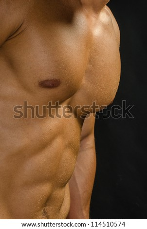 Image of a man with perfect abdominal muscles against a black background