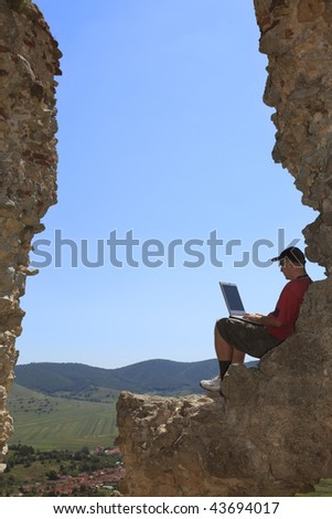 Image of a man working on a laptop outdoors. - stock photo