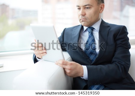 Image of a mature entrepreneur choosing the most suitable business solution via tablet - stock photo