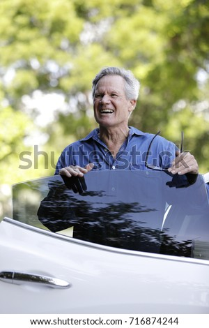Image of a mature man getting out of the passenger side of a car