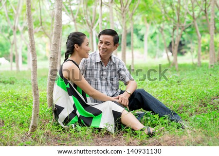 Image of a middle-aged couple sitting on the ground in the park - stock photo