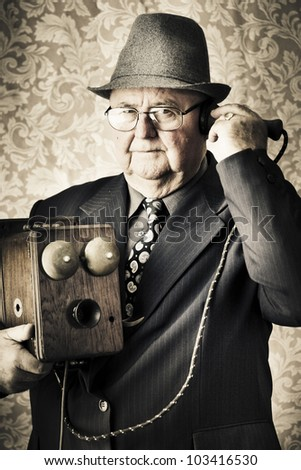 Image of a old fashioned vintage business man standing in a office communicating to the exchange through a retro box telephone in a technology concept - stock photo