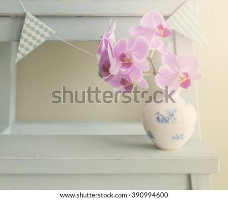 Image of a pastel colored still life with orchids and bunting.  - stock photo