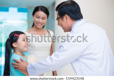 Image of a pediatrician having an appointment with a little child and her mom on the foreground