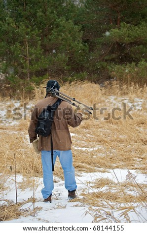 Image of a photographer with his camera bag and tripod heading out to the woods to take pictures on a cold, snowy winter day with copy space.