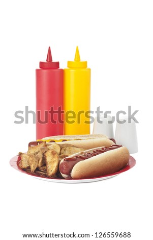 Image of a plate with hotdog sandwiches and potato wedges with condiments on the side - stock photo