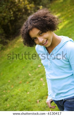 image of a pretty biracial girl in apark setting - stock photo