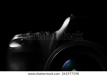 Image of a professional modern DSLR camera low key image - Modern DSLR camera with a very wide aperture lens on in a dark space. Top part of a camera is visible and the rest goes into the shadow - stock photo