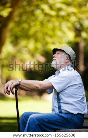 Image of a retired old man sitting on the bench looking at the sky, shallow depth of field - stock photo