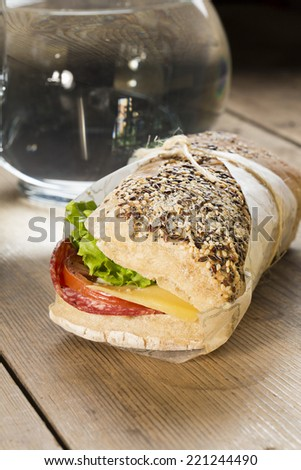 Image of a sandwich with red tomato, fresh lettuce and cheese, covered with sesame seeds wrapped in wrapping paper, on a wooden table - stock photo