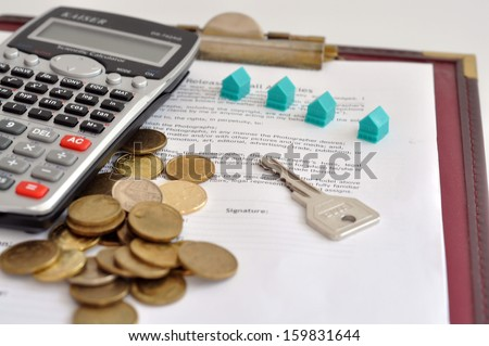 image of a scale house and mortgage forms for the people buying a house. - stock photo