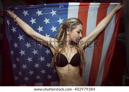 image of a sexy slim blond woman hold in hands big American flag Skinny body of cute young adult girl with black pantyhose on legs stand in corridor perspective in dark background - stock photo