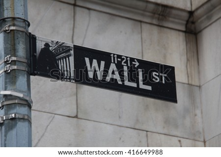 Image of a sign for Wall Street taken in New York with rain drops on sign. White letters green background. On post. - stock photo