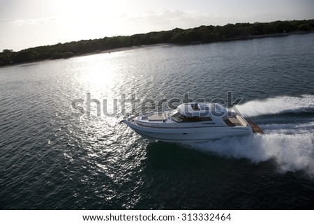 Image of a small motor boat sailing in a sea across a coast on a sunny day