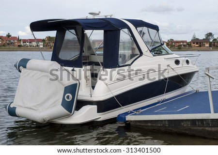 Image of a small transport motorboat with blue roof tied to the pier